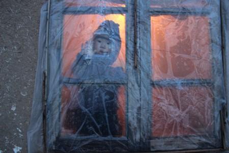 Зимой окна дома закрываются полиэтиленовой пленкой. Гүлбүбү оставляет маленькое отверстие для своего любопытного внука, чтобы он мог наблюдать за жизнью на улице.