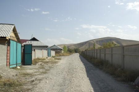 Слева - жилмассив. Справа - забор кладбища.