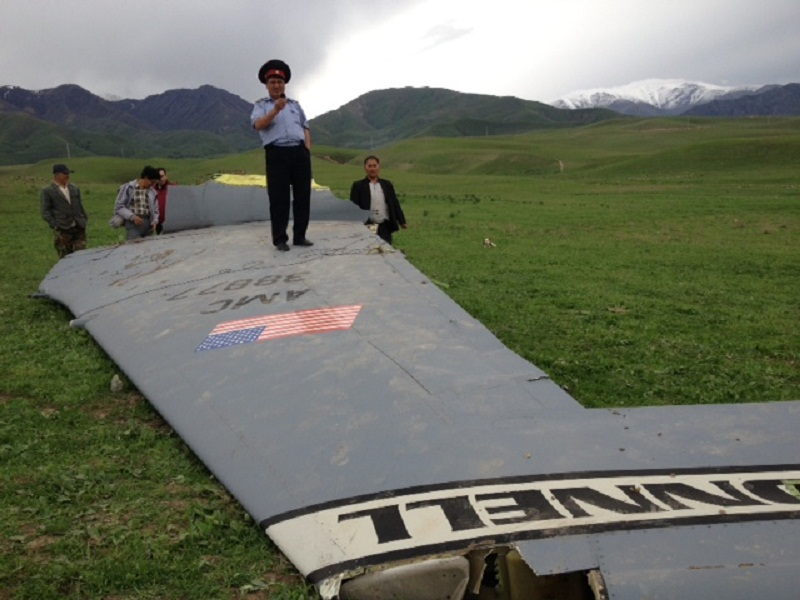 Милиционер охраняет крыло только что разбившегося самолёта, 3 мая 2013 года. Фото: Эльдияр Арыкбаев
