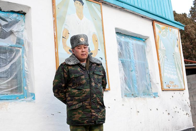 Кыргызский полковник Эрзат Шамшиев стоит у стены, обстрелянной из автоматов Калашникова во время перестрелки у водозабора.