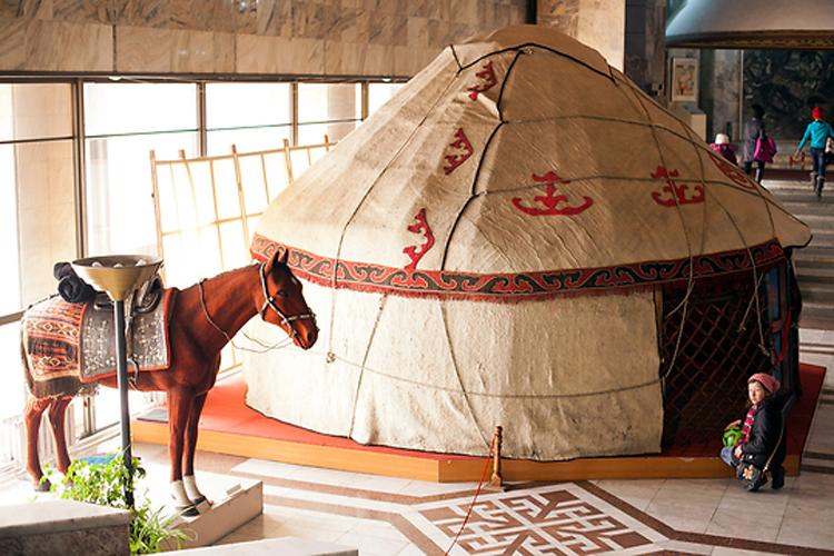 Ребенок заглядывает в модель традиционного дома кыргызских кочевников в натуральную величину, называемого юртой.