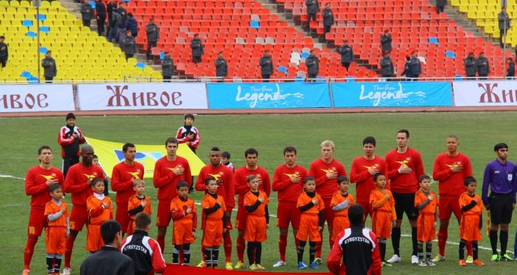 Футболисты сборной Кыргызстана поют гимн перед матчем против сборной Макао. Март 2013 года.