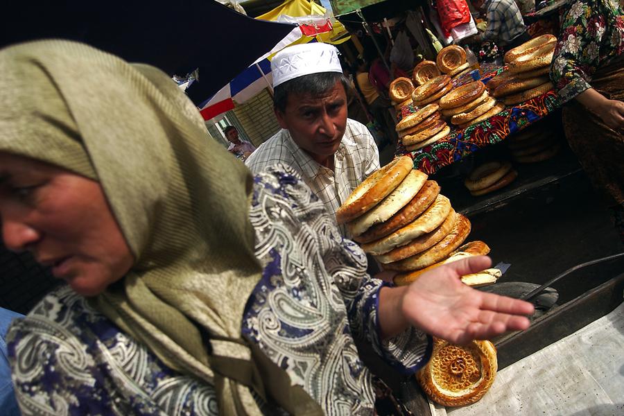 Мужчина складывает лепешки на тележку, с которой пойдет по рынку в поисках покупателей.