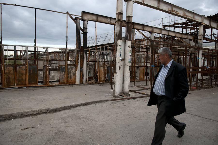 Мужчина идет вдоль разрушенного, некогда крытого, рыночного павильона.
