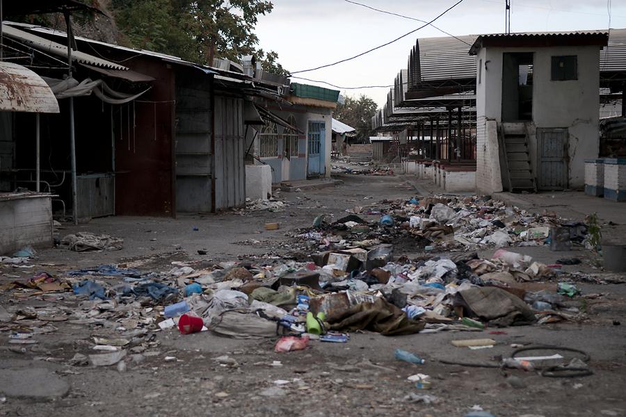 На бетонных дорожках рынка валяется мусор.