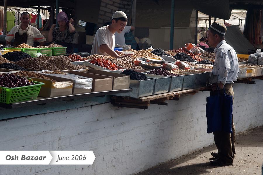 Покупатель в традиционной черной узбекской тюбетейке остановился у прилавка с орехами и сухофруктами (июнь 2006 г).