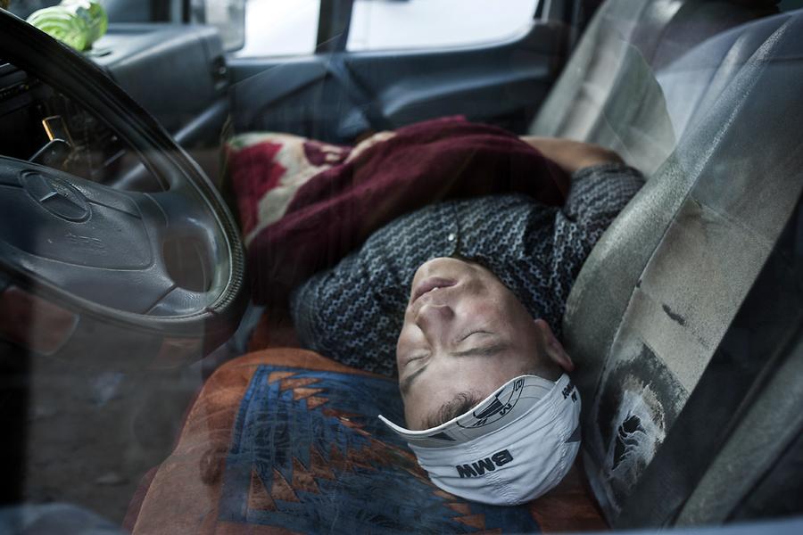 Пассажир отсыпается на переднем сиденье во время шестичасовой остановки перед сложным горным отрезком пути до Бишкека.