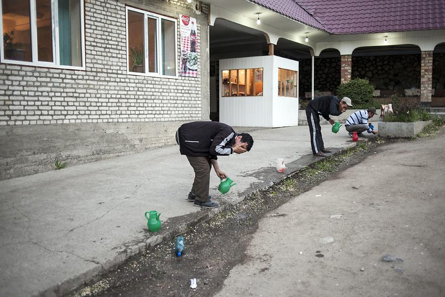Пассажиры умываются во время остановки на отдых на территории Кыргызстана.