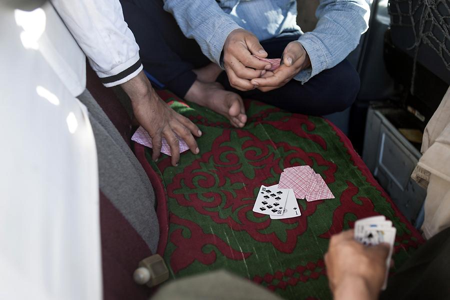 Долгие часы путешествия в переполненном микроавтобусе пассажиры коротают за игрой в карты.
