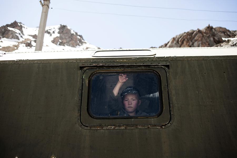 Кыргызский мальчишка смотрит из семейного вагончика на направляющихся в Россию трудовых мигрантов.