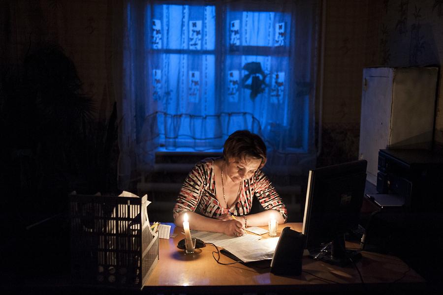 При свете свечи из-за отключения электричества менеджер кафе Лена Зименко заполняет для водителя бланк российской страховки.