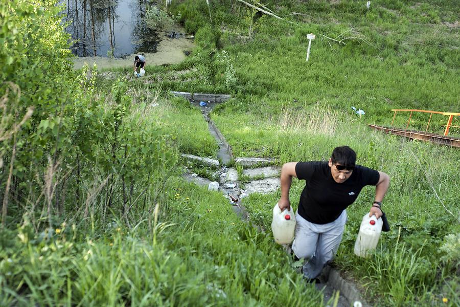 Водители набирают воду из ручья во Владимирской области под Москвой, чтобы залить в потекший радиатор.