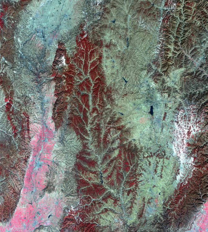 Цепочка гор близ города Чанчжи. Розовым цветом отмечены пахотные земли на левой стороне снимка. Справа изображены снежные верхушки гор, выделенные белым цветом, а красным отмечена растительность на горной поверхности.
