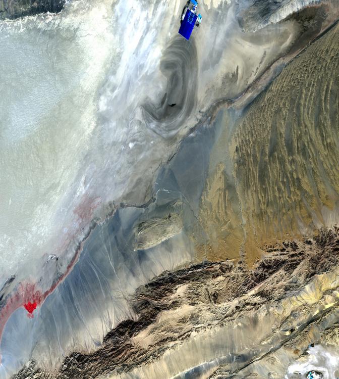 Пустыня на западе Китая. Синим и красным цветами отмечены искусственные водоёмы. В форме уха на снимке изображено высохшее озеро, границы которого размылись ветрами.