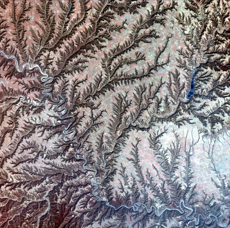 Плоскогорье на фото поделено на множество частей, так как поверхность была поражена эрозией. Изображенная длинным зигзагообразным течением река разделяет плоскогорье на две части.