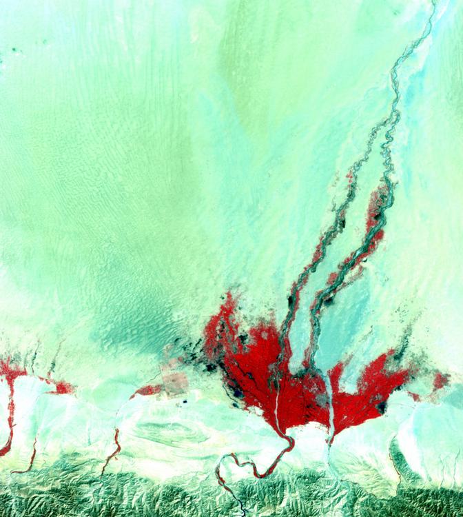 На этом фото изображены горы и маленький водоем в пустыне.