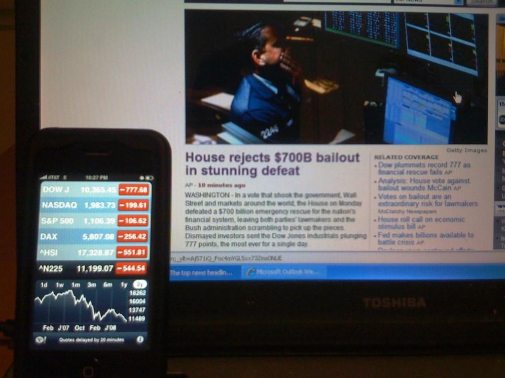 Мировой финансовый и экономический кризис стал главным потрясением 2000-х. На экране смартфона: показатели падения крупнейших фондовых бирж в США и Европе.  На экране компьютера: новость об отказе Конгресса США выделить 700 миллиардов США на поддержание банков, которые в итоге потерпели банкротство.