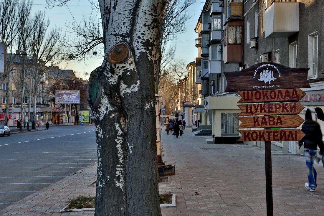 На одной стороне улицы - билборд с выборами в народный совет ДНР. На другой - Львовская мастерская шоколада