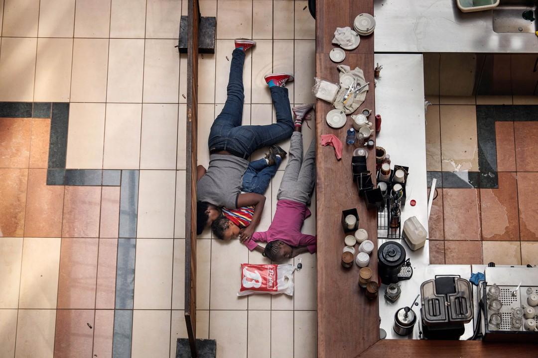 II место в категории «Горячие новости», Тайлер Хикс (Tyler Hicks, США) «Убийство в молле Вэстгейт», 21 сентября 2013. Найроби, Кения. Женщина и двое детей прячутся во время атаки на торговый центр Вэстгейт. Они не пострадали в конечном итоге.  21 сентября вооруженные люди в масках открыли огонь по торговому центру  «Вестгейт» в Найроби. Престижный торговый центр был популярен среди экспатов и Кенийской элиты. Во время осады, которая продолжалась 4 дня, погибло как минимум 60 человек, около 200 получили ранения. Четверо основных виновников нападения были убиты, ряд других людей были позже позже расценены как соучастники. Все четверо боевиков были сомалийского происхождения. Сомалийская джихадистская группа «Аль-Шабаб» взяла на себя ответственность за нападение, заявив, что это было предупреждение Кении вывести свои войска из Сомали. Кенийские войска в Сомали были частью Африканского союза миротворческих сил в конфликте с боевиками.