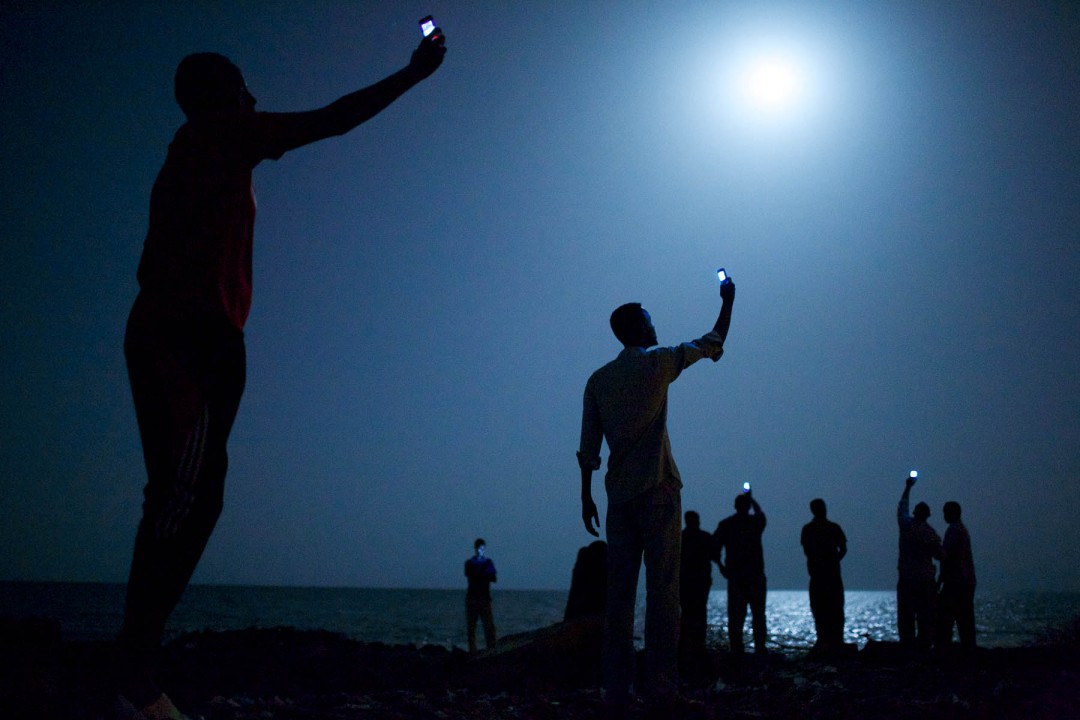 I место в категории «Современные проблемы», Джон Стенмайер (John Stanmeyer, США) «Сигнал». Африканские мигранты на берегу Аденского залива возле Джибути (Восточная Африка). В ночное время они пытаются поймать сигнал недорогой мобильной связи из соседнего государства Сомали, чтобы связаться со своими родственниками.