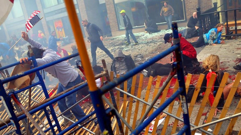 I место в категории «Горячие новости», Джон Тлумаки (John Tlumacki, США) «Взрывы на бостонском марафоне»,15 апреля 2013 года. Бостон, США. Карлос Аррендондо (слева) взбирается по баррикадам на улице Бойлсон, чтобы добраться до людей, пострадавших от первой из двух бомб, которые взорвались возле финишной прямой на Бостонском марафоне 15 апреля. Бомбы взорвались с интервалом в 12 секунд, убив 3 человек и покалечив как минимум 264. Победители пересекли финишную прямую несколькими часами ранее, но оставались еще тысячи человек, а также зрители на улице.  18 апреля ФБР выпустило фотографии и кадры из видео двух подозреваемых. Позднее они были опознаны как чеченские братья, Джохар и Тамерлан Царнаевы. Вскоре после того, как они были опознаны, братья, как утверждают, убили офицера полиции и угнали машину. Тамерлан погиб в последующей перестрелке с полицией, Джохар был арестован несколькими часами позже.