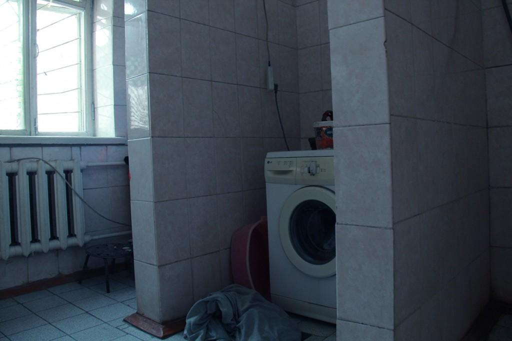 В этой комнате находится душевая и стиральная машина.