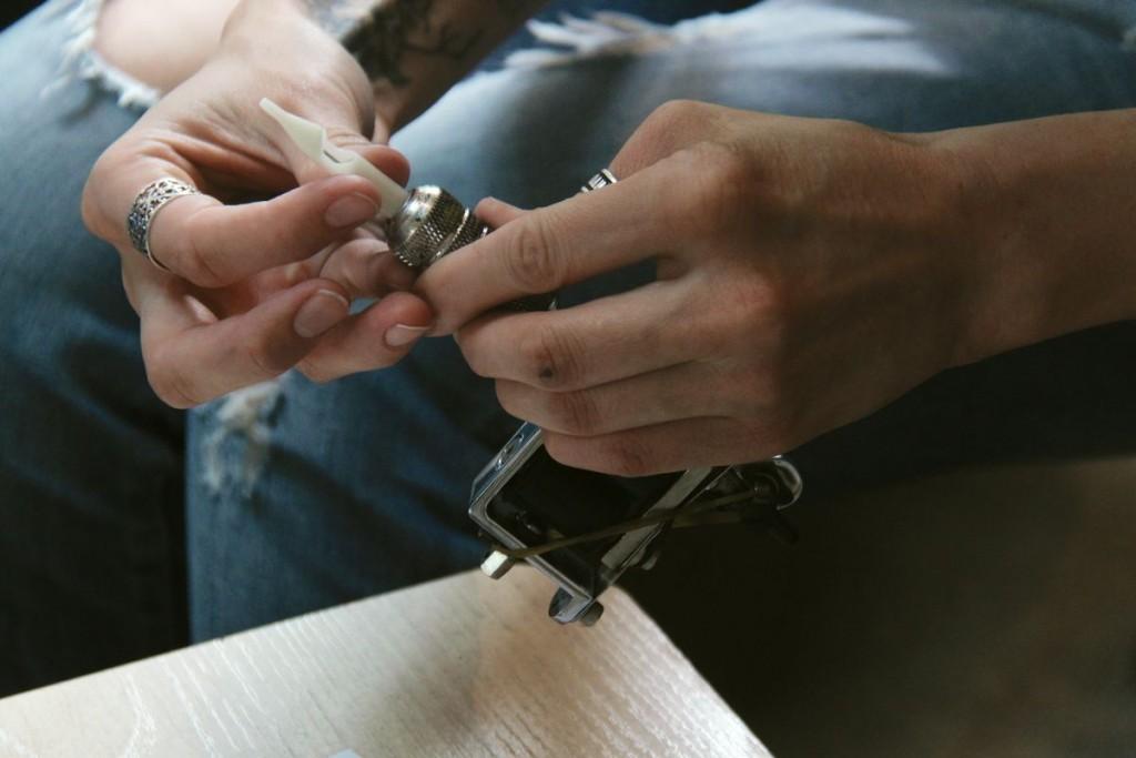 Мастер вставляет насадку для игл в татуировочную машинку.