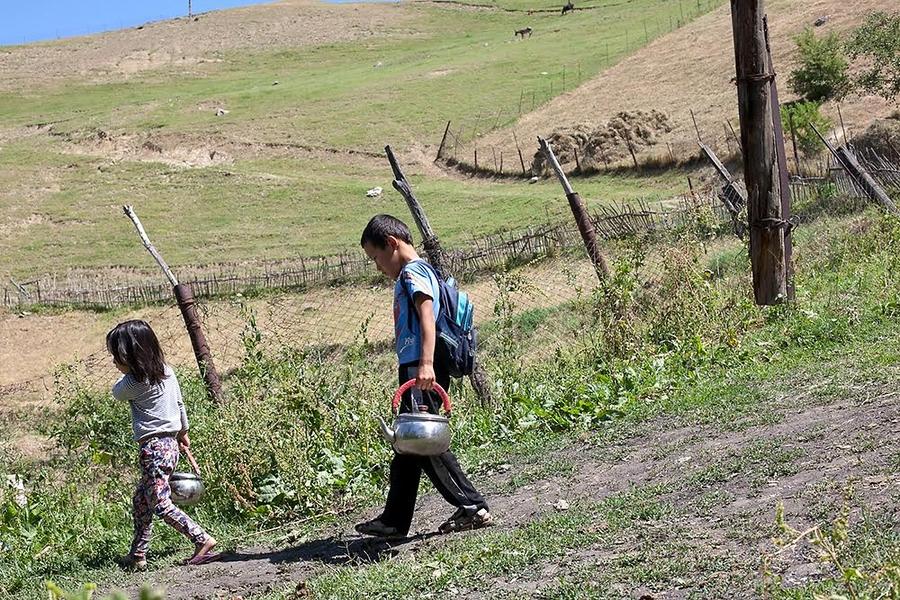 Дети, живущие в находящемся ниже могильника районе, берут воду из местного источника. (Фото: Дэвид Триллинг)