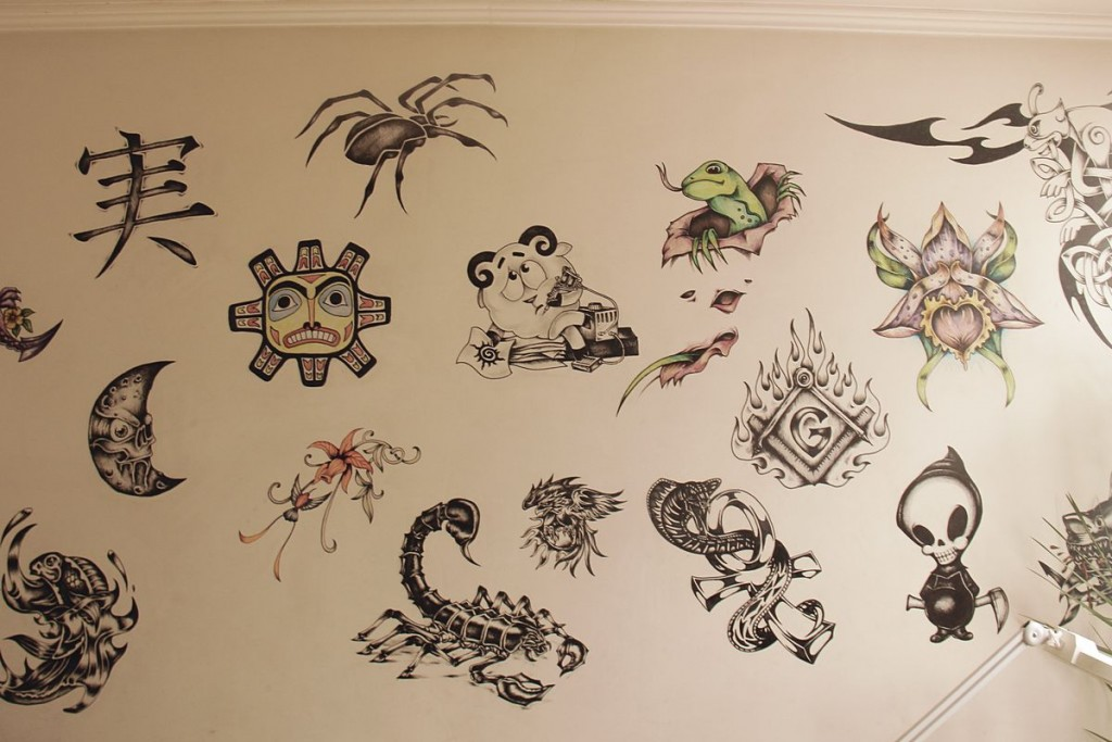 На стенах висят эскизы татуировок .
