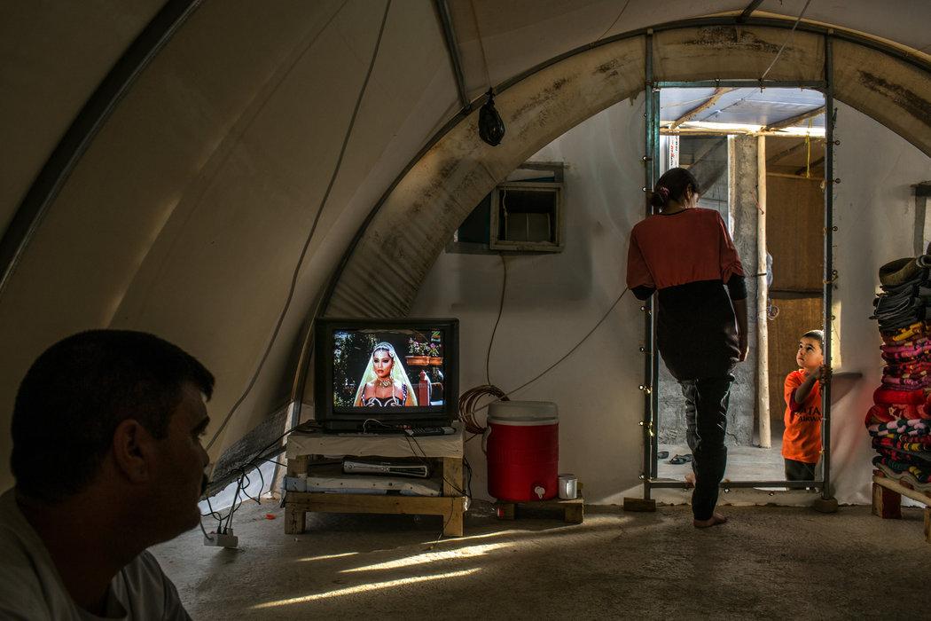 Справа 15-летняя девочка, которая пожелала называться «Ф» в репортаже — она находится в этом помещении с отцом и 4-летним братом. «Каждый раз, когда он приходил насиловать меня, он молился», — говорит «Ф», которую год назад взяли в плен участники ИГИЛа на горе Синжар, а потом продали иракскому солдату. Автор: Маурисио Лима / «Нью-Йорк Таймс».