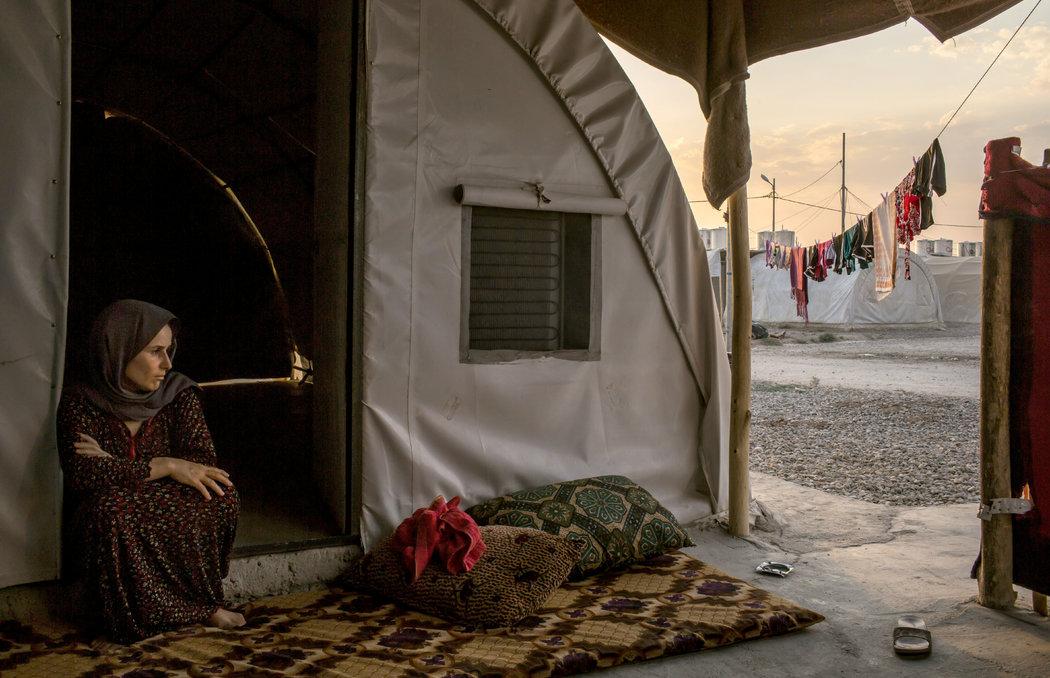 40-летняя Айшан Али Салех сидит на окраине лагеря беженцев в Дохуке. Она жила в Коджо — одном из поселений на крайнем юге горы Синджар — которое было завоевано бойцами ИГИЛа. Автор: Маурисио Лима / «Нью-Йорк Таймс».