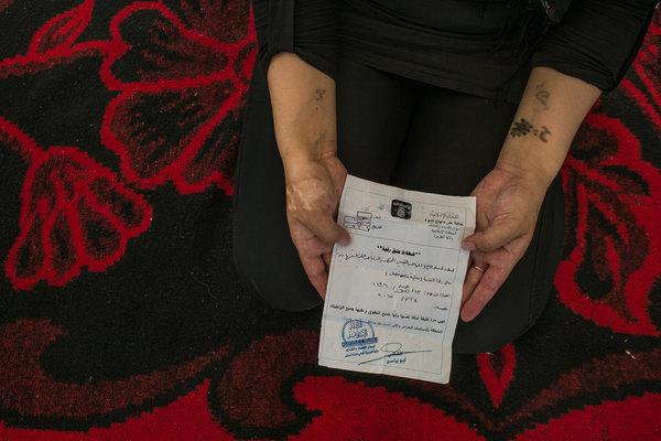 25-летняя езидка показывает «сертификат об эмансипации», который ей вручил ливиец, освободивший её. Он объяснил, что только что прошел тренировки шахидов и планировал подорвать себя, и оказался рядом с ней, чтобы освободить. Автор: Маурисио Лима / «Нью-Йорк Таймс».