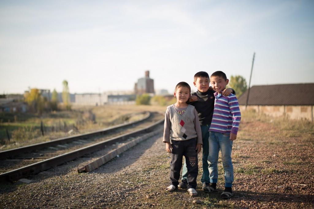 Токмок, Кыргызстан. Трое мальчишек играют рядом с железнодорожными путями.