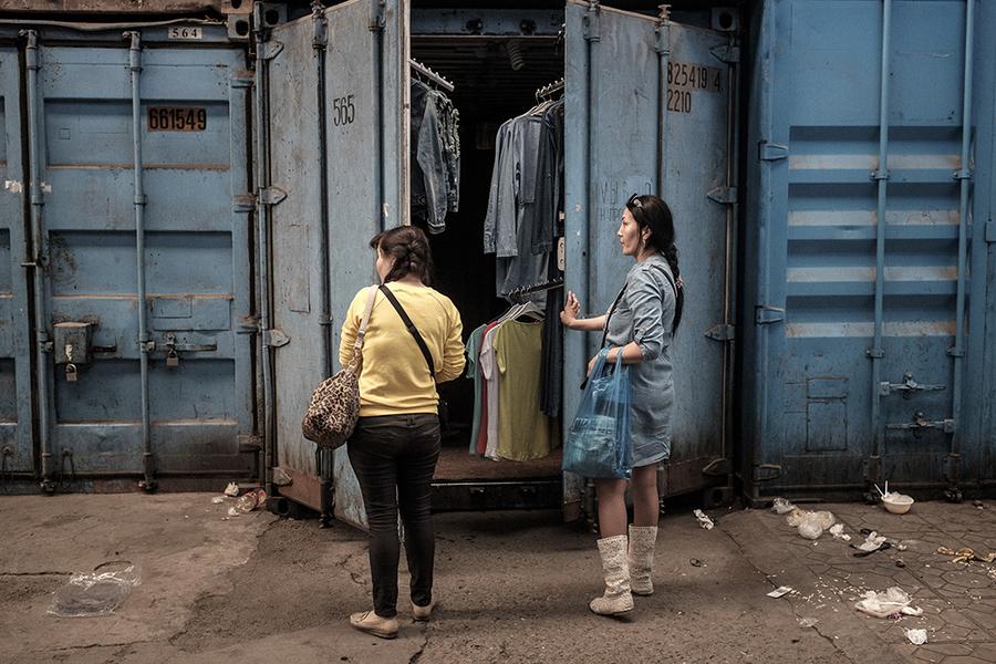 Торговцы закрывают свои контейнеры в 4:00 пополудни на одном из проходов рынка.