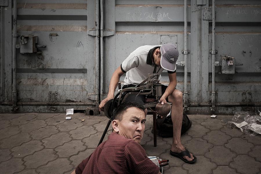 Сапожник чинит обувь, работая на примитивном станке внутри рынка.