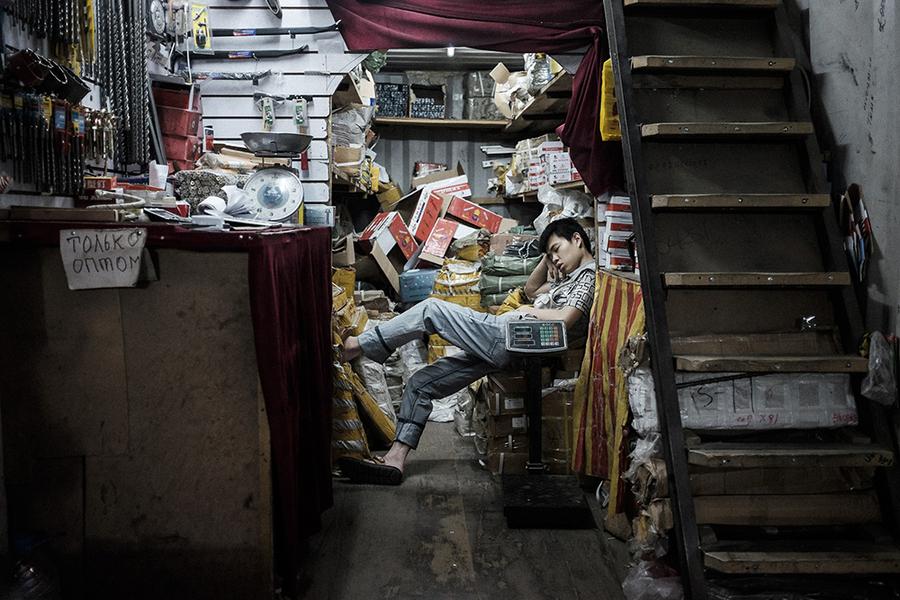 Молодой торговец дремлет посреди рынка «Джунхай», который является частью «Дордоя».