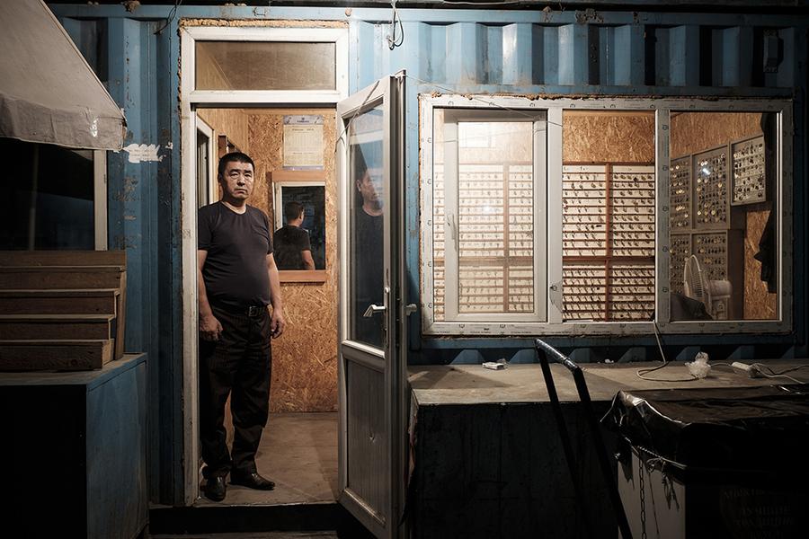 Медер — 52-летний начальник охраны рынка — стоит в проеме главного охранного пункта в свою ночную смену.