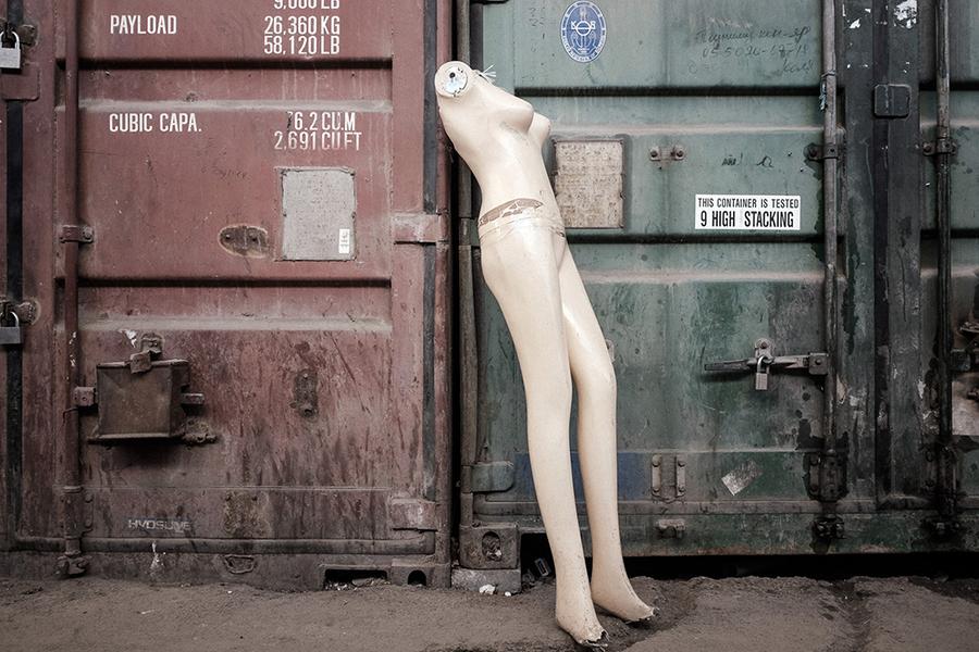 Голый манекен прислонен к одному из тысяч контейнеров рынка.