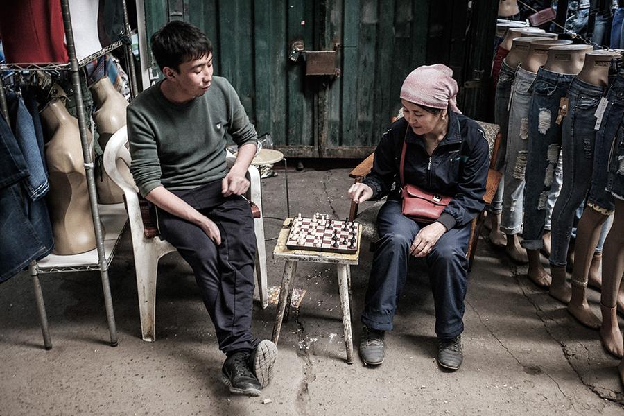 Торговцы играют в шахматы, пока клиенты и хозяева контейнеров заняты обедом.