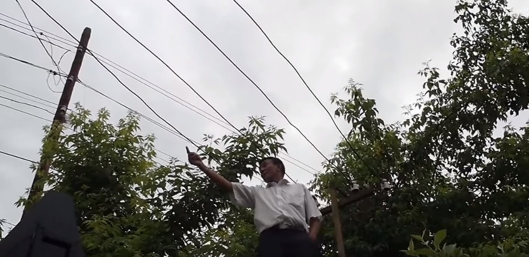 Таалай Айдаров на заборе. Скриншот из видео.