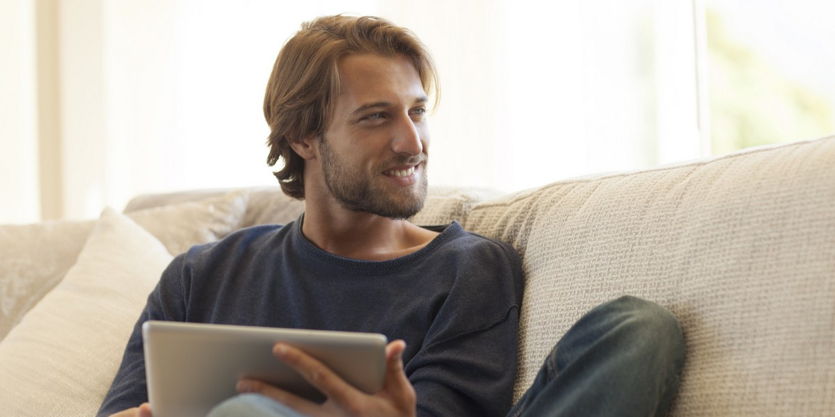 Man using tablet computer on sofa