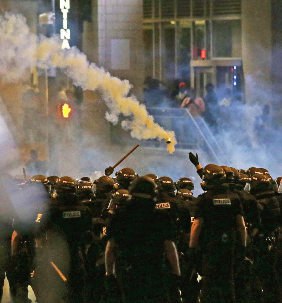 Полицейские успокаивают толпу слезоточивым газом. Фото: Gerry Broome/Associated Press