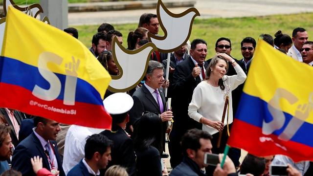 Сантос на фоне колумбийского флага и голубей мира