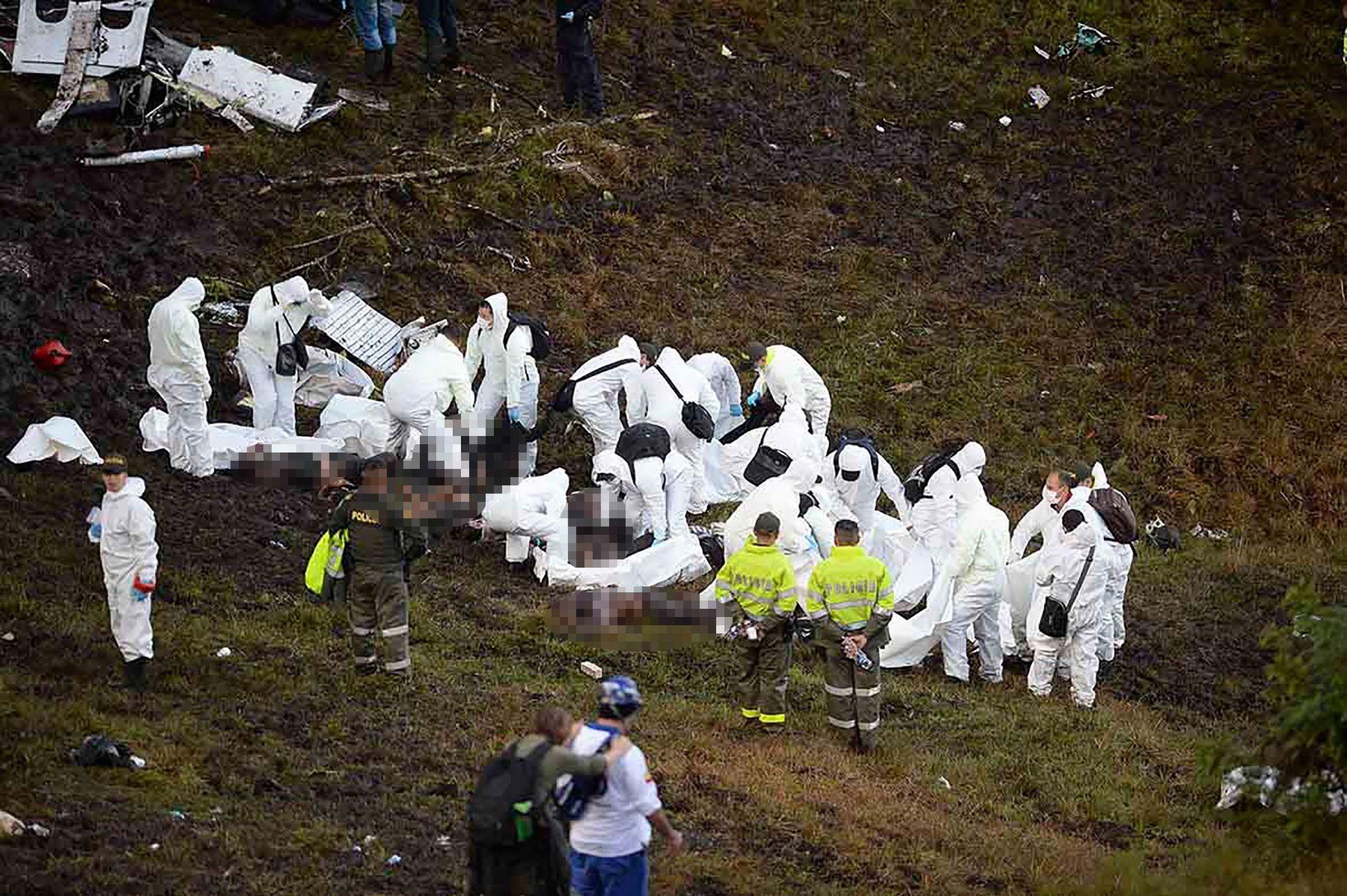 судебно-медицинские эксперты извлекают из под обломков тела погибших. Фото: AP