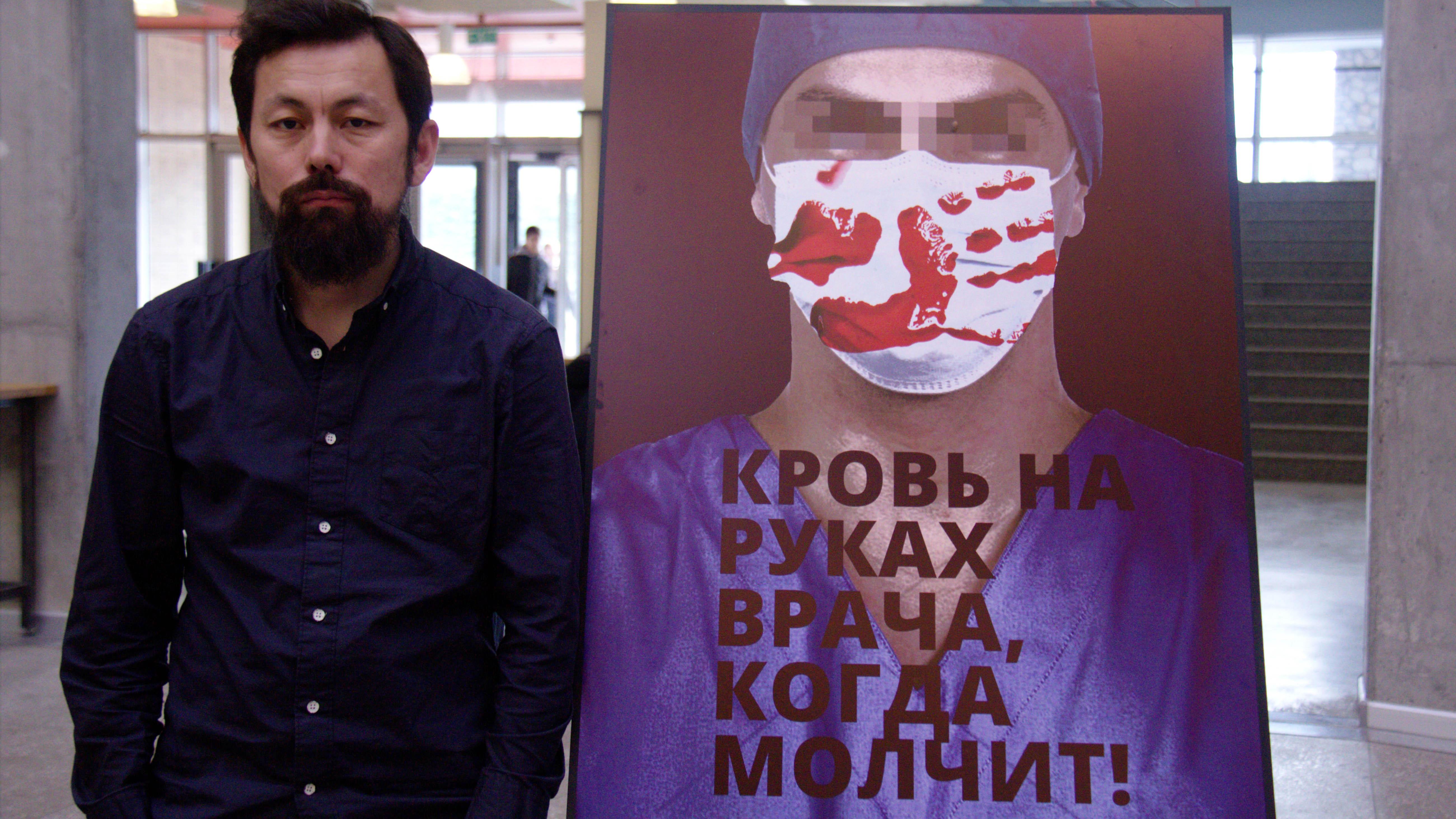 Дизайнер Марсель Шейшенов со своим плакатом.